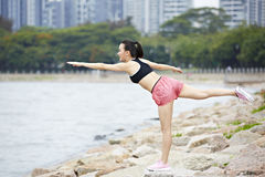 Young asian woman doing balancing exercise royalty free stock image