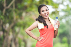 Young asian woman after doing excercise outdoor in a park, holdi Royalty Free Stock Images