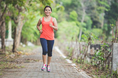 Young asian woman doing excercise outdoor in a park, jogging Stock Photos
