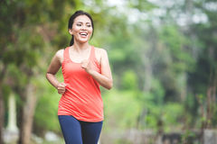 Young asian woman doing excercise outdoor in a park, jogging Royalty Free Stock Image