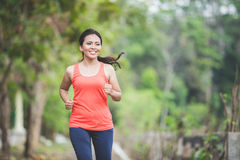Young asian woman doing excercise outdoor in a park, jogging Royalty Free Stock Photography