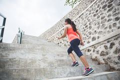 Young asian woman doing excercise outdoor in a park, jogging up. A portrait of a young asian woman doing excercise outdoor in a park, jogging up and down the Stock Images