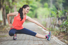 Young asian woman doing excercise outdoor in a park, stretching Stock Photography