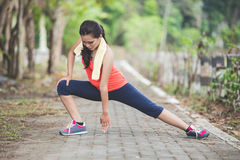 Young asian woman doing excercise outdoor in a park, stretching Stock Photos