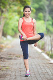 Young asian woman doing excercise outdoor in a park, stretching Stock Photo