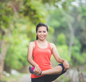 Young asian woman doing excercise outdoor in a park, stretching Royalty Free Stock Image