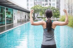 Young asian woman doing exercise by the pool in hotel or resort