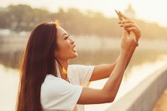 Woman selfie outdoors. Young asian woman doing selfie on city river background at sunny morning Royalty Free Stock Photos