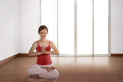 Young asian woman doing yoga in a lotus position Royalty Free Stock Photos