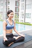 Young asian woman doing yoga moves or meditating by the pool, Royalty Free Stock Photography