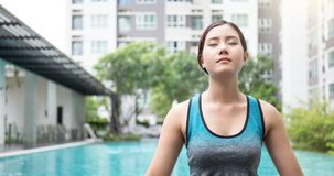 Young asian woman doing yoga moves or meditating by the pool, Royalty Free Stock Images
