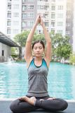 Young asian woman doing yoga moves or meditating by the pool, royalty free stock photos