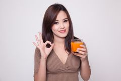 Young Asian woman drink orange juice show OK sign. Royalty Free Stock Images