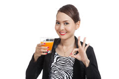 Young Asian woman drink orange juice show OK sign Royalty Free Stock Image