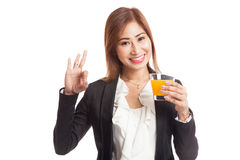 Young Asian woman drink orange juice show OK sign Royalty Free Stock Images