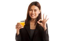 Young Asian woman drink orange juice show OK sign. Royalty Free Stock Photos