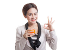 Young Asian woman drink orange juice show OK sign. Royalty Free Stock Photos