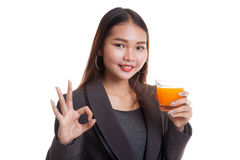 Young Asian woman drink orange juice show OK sign. Stock Image