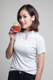 Young Asian woman drink tomato juice. Young Asian woman drink tomato juice on gray background Royalty Free Stock Photos