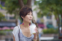Young asian woman drinking beverage in plaza Stock Images