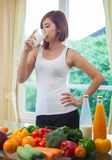 Young asian woman drinking milk. In kitchen Royalty Free Stock Photo