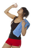Young Asian woman drinking water. Portrait of attractive Asian woman drinking mineral water from bottle  after fitness class. Isolated on white, studio shot Royalty Free Stock Images