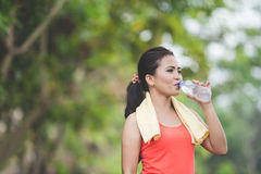 Young asian woman drinking water after doing excercise outdoor i Royalty Free Stock Images
