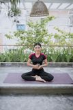 Young asian woman drinking water from glass after exercise yoga and meditation.  royalty free stock image