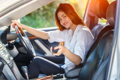 Young asian woman driver driving a car on the road in countryside. Young asian woman driver driving a car on the road in countrye and hand presses on the remote Stock Photo