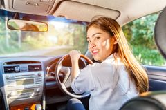 Young asian woman driver driving a car on the road in countryside royalty free stock photography