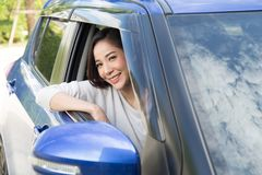 Free Young Asian Woman Driving A Car And Smile Happily With Glad Positive Expression During The Drive To Travel Journey. Stock Photos - 156619013