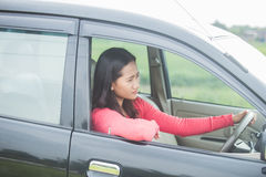 Young Asian woman driving a car with serious face Stock Images