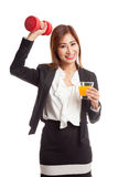 Young Asian woman with dumbbell drink orange juice Stock Photography