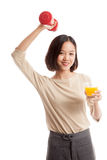 Young Asian woman with dumbbell drink orange juice Royalty Free Stock Images