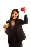 Young Asian woman with dumbbell drink orange juice. Stock Photography
