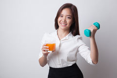 Young Asian woman with dumbbell drink orange juice. Stock Image