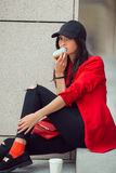 Young asian woman eating fast food outdoors Stock Photos