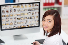 Young Asian woman editing photographs Royalty Free Stock Photo