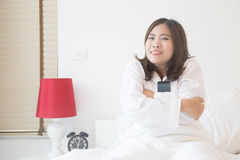 Young asian woman embrace smartphone on the bed in the morning Royalty Free Stock Photography