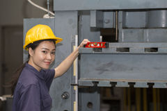Young asian woman engineer set up and testing old machine Royalty Free Stock Photos