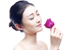 Young asian woman enjoying fragrance of red rose Royalty Free Stock Image