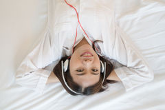 Young asian woman enjoying the music at bed Royalty Free Stock Photos