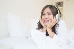Young asian woman enjoying the music at bed Stock Photo