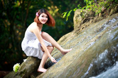 Young asian woman enjoying the pure waters of a mountain river i Stock Photo
