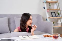 Young asian woman enjoying a tea break and snack while working a. T home Royalty Free Stock Photos