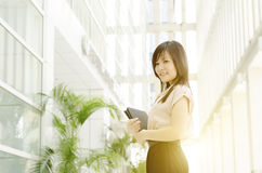 Young Asian woman executive at office. Young Asian woman executive smiling and walking at an office environment, beautiful golden sunlight at background Royalty Free Stock Images