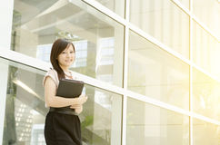 Young Asian woman executive smiling. And standing at an office environment, beautiful golden sunlight at background Stock Images
