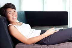 Young Asian woman executive watching television Stock Images