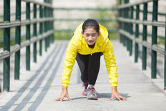 Young asian woman exercising outdoor in yellow neon jacket, gett. A portrait of a young asian woman exercising outdoor in yellow neon jacket, getting ready for Royalty Free Stock Photography