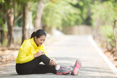 Young asian woman exercising outdoor in yellow neon jacket, injured her foot stock images